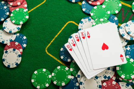 royal flash on cards and poker chips on green casino table. success in gambling Stock Photo