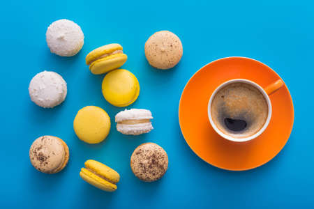 decaf: Orange coffee cup with sweet colorful macarons cake on a blue background, top view Stock Photo