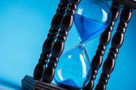 close up of hourglass on a blue background