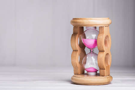 close up of hourglass on a white wood table Stock Photo