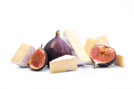a piece cheese head brie cheese with figs isolated on white background