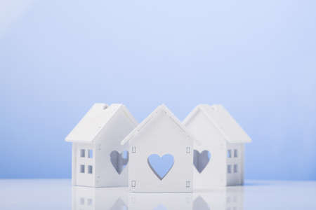 white house model icon with heart symbol on blue background. buying a house concept