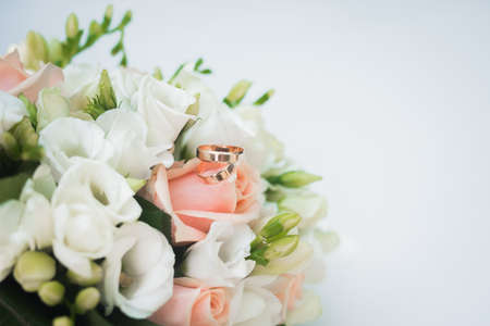 wedding flower bouquet on white table. rose flowers decoration. golden rings