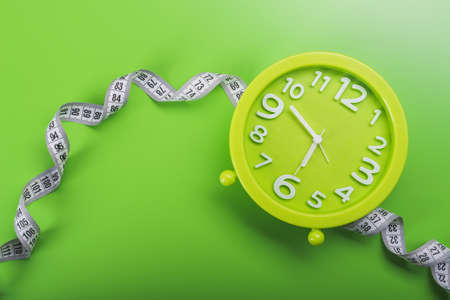 clock with measuring tape. diet concept. top view green background