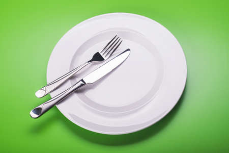 Empty white plate with knife and fork on green background. view from top