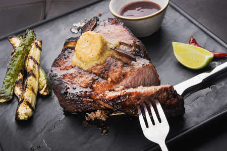 grilled steak tee bon with spices , knife and fork, on black slate board. delicious restaurant food