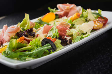 tasty salad with prosciutto, salan and peach on white dish. vegetarian healthy food