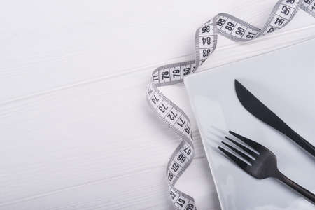 fork and knife with white measuring tape. diet food background