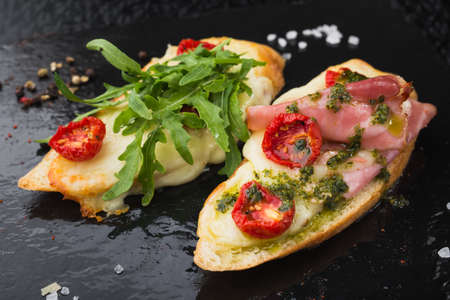 hams: appetizer bruschetta with tomato and bacon, chesse on black slate board