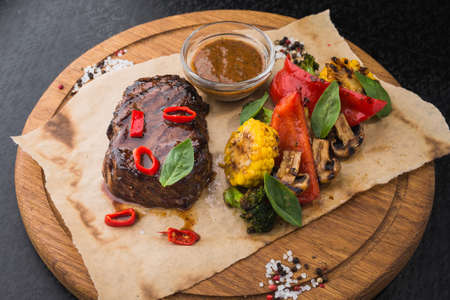 hot steak with vegetables and pepper, corn and mushrooms on wooden board. delicious snack at the restaurant Stock Photo