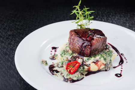 steak medallion with tomatoes and sauce on a white plate. restaurant food. black background