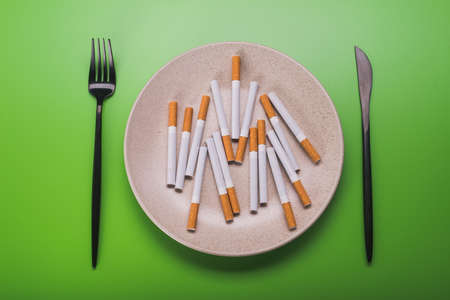 concept idea harmfulness of smoking for breakfast with black fork and knife Stock fotó