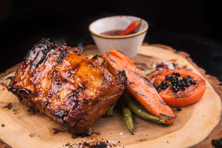 grilled meat ribs with vegetables on wooden cutting board