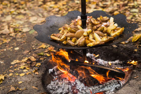 juicy roast potatoes on a metal frying pan, under the wood fire, homemade food at the festivals meal Foto de archivo