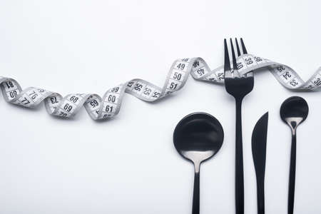 Diet concept, black fork and measuring tape isolated on white background