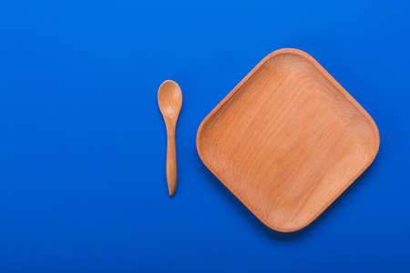 Empty wood set with plate and small spoon on blue backgound