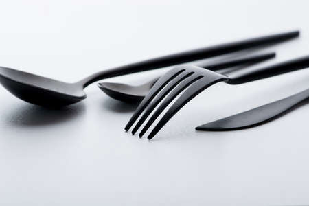 Cutlery set with black fork, knife and spoon on white background Stock Photo