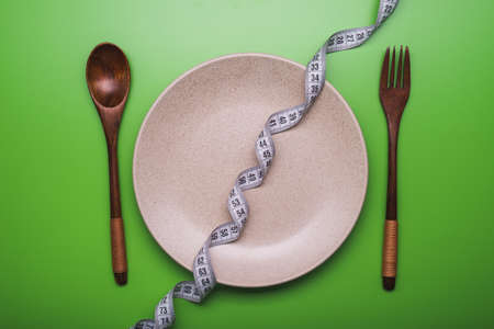 weight loss concept. plate with fork, knife and spoon on background Stock Photo