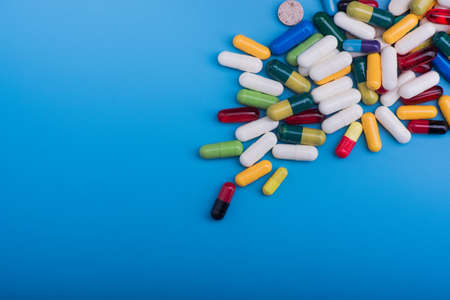 Colored pills and medical capsule on blue background