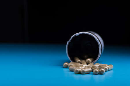 Herbal pills on a blue background. Bad supplement