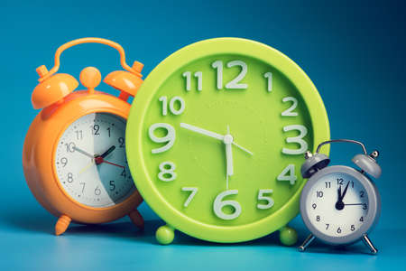 Three alarm clock withnumbers on blue background. time concept Stock Photo