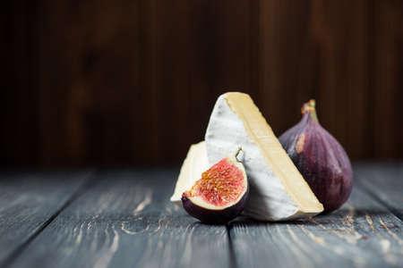 木製のテーブルにイチジクとチーズのカマンベールやブリーの白い部分 写真素材