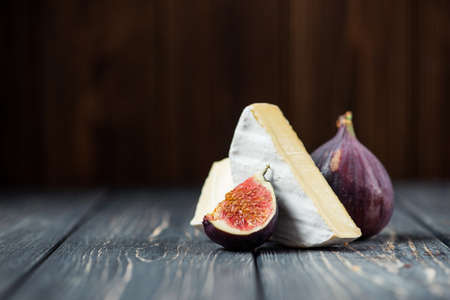 white pieces of camembert or brie cheese with fig on a wooden table
