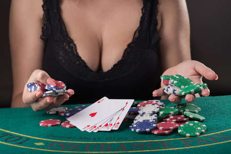sexy woman in black underwear with big boobs playing poker game at the table