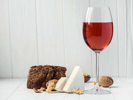 a glass of red wine with cheese brie, bread on a white wooden background Stock Photo