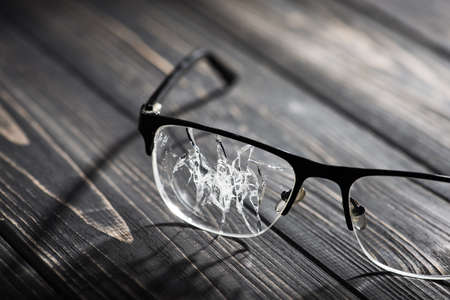 broken glasses on a wooden table. concept of failure in business