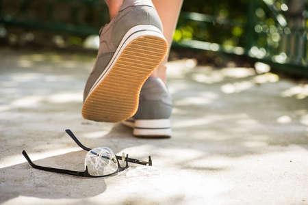 여자 도보로 안경에 밟은. 거리에서 불행한 사건. 아스팔트에 깨진 안경
