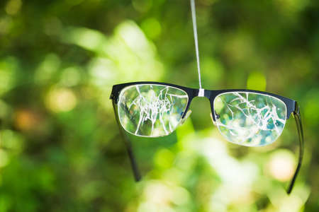 broken glasses on the green background of nature. concept of failure on the street Stock Photo