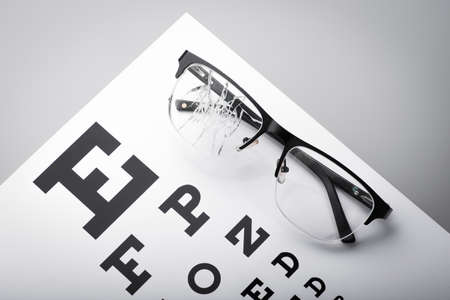 poor eyesight. cracked glasses against the background of the eye chart