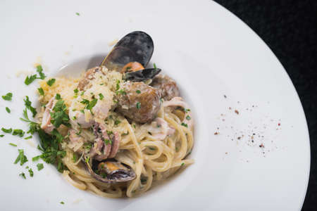 seafood pasta with squid and mussels in a white plate. dish at the restaurant Stock Photo