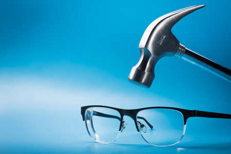 grande martello di metallo con gli occhiali su sfondo blu. sbarazzarsi di occhiali e vista scarsa