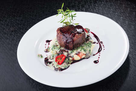 steak medallion with tomatoes and sauce on a white plate. restaurant food. black background Фото со стока - 90879417