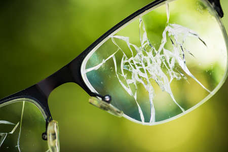 broken glasses on the green background of nature. concept of failure on the street Stockfoto