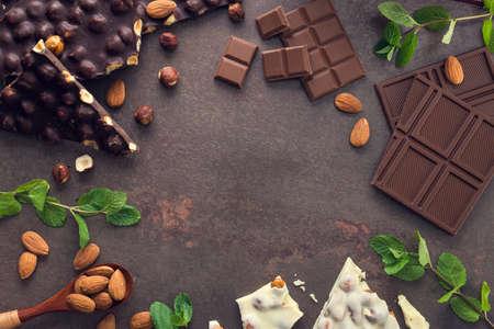 Smakelijke chocoladerepen met noten, verse munt en amandel op een stenen achtergrond. Zoet eten Stockfoto