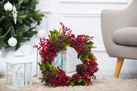 holiday christmas wreath with cones and red berry with candlestick lantern