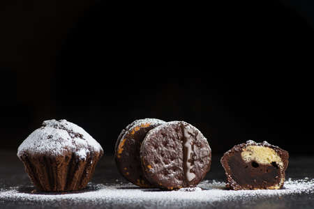 Chocolate cake, cupcake and sweet cookies with powder on a black background Stock Photo