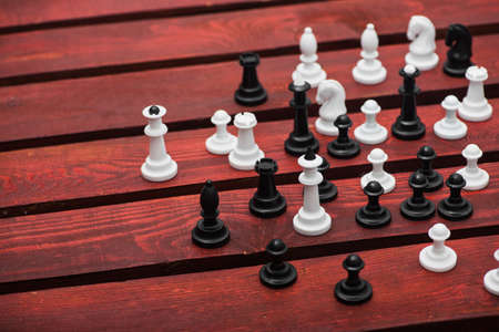 A group of white and black chess pieces on a red wooden table 写真素材
