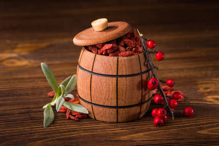 red dried goji berries contain many useful substances, vitamins and minerals in wood barrel Stock Photo