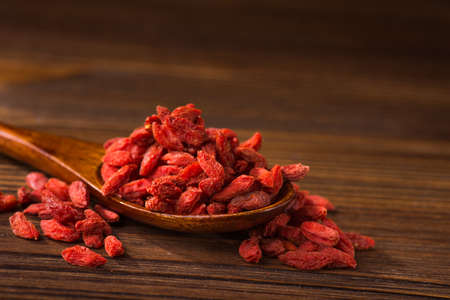 Tibetan goji berries contain many useful substances, vitamins and minerals on wooden table Stock Photo