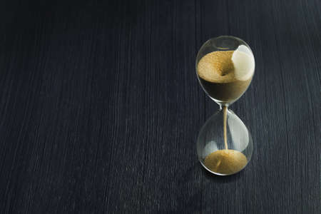 Retro hourglass with two transparent flask with sand on background. Time passing concept