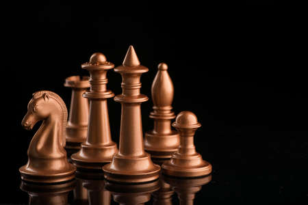 A series of gold chess pieces on a black glossy surface. Game set on dark background.