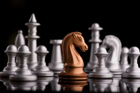 golden chess knight horse against the background of the general group of figures, black background Stok Fotoğraf