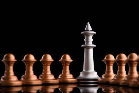 chess king stand with pawn on black background. unfair confrontation Stock Photo