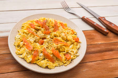 Breakfast of scramble with salmon fish in a plate on a wood table. rural food style Banco de Imagens - 93866093