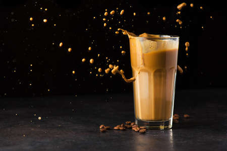 Iced latte coffee glass with splash on a black background