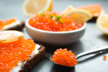 delicious red caviar with sandwich and fresh lemon slice on a table. seafood luxury snack